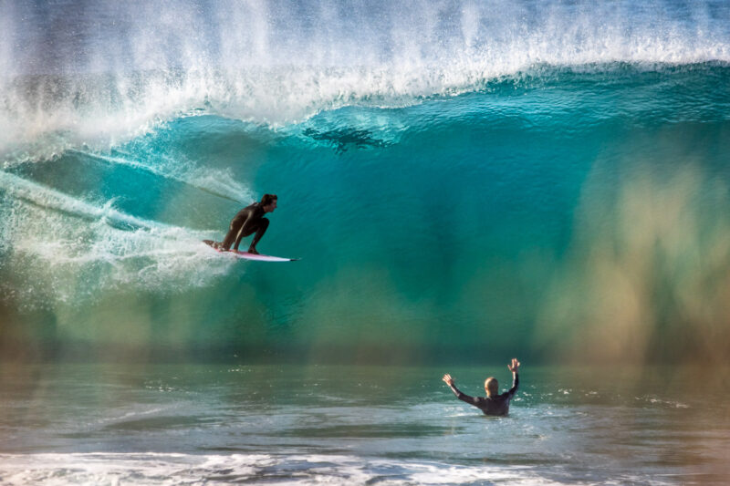 Surfer in barrel while friend cheers him on
